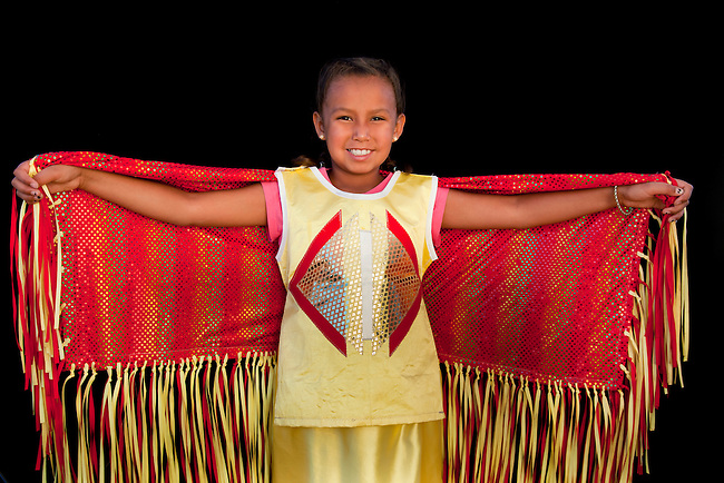 Girls shows off red and yellow outfit who is a fancy shawl dancer. Ruthee Rae Baker (Shoshone-Bannock Ponca)