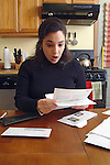 young adult woman sitting at kitchen table shocked and stressed by pile of unpaid bills.