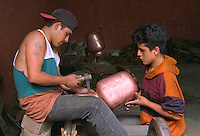 Copper worker shaping vessel with help of assistant. Santa Clara del Cobre Michoacan Mexico.