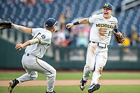 Michigan Wolverines first baseman Jimmy Kerr (15) celebrates with teammate Riley Bertram (12) following Game 11 of the NCAA College World Series against the Texas Tech Red Raiders on June 21, 2019 at TD Ameritrade Park in Omaha, Nebraska. Michigan defeated Texas Tech 15-3 and is headed to the CWS Finals. (Andrew Woolley/Four Seam Images)