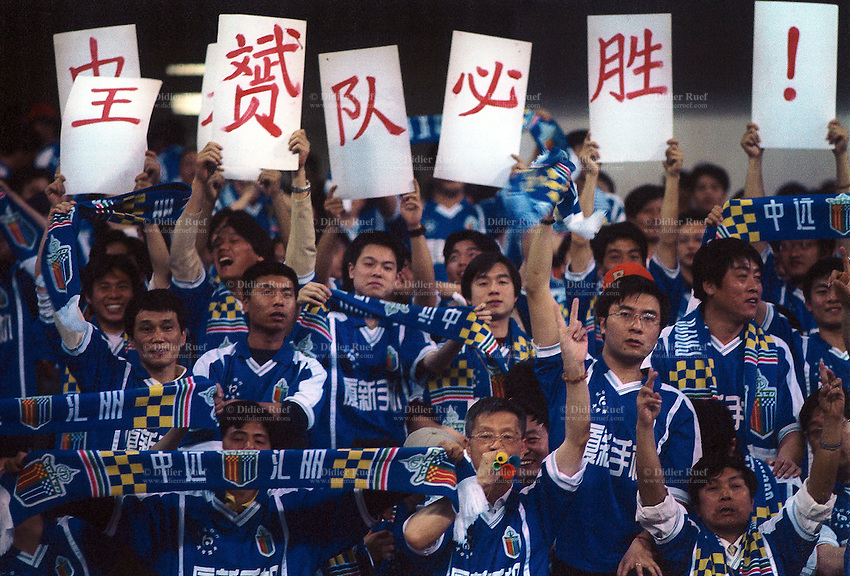 China. Shanghai. Shanghai stadium. Supporters from the Shanghai Cosco Huili Football Club before the start of the game make the sign of victory by using their fingers. © 2002 Didier Ruef