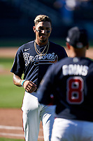 Atlanta Braves Johan Camargo (17) gets his hat and glove from Ryan Goins (8) during a Major League Spring Training game against the Boston Red Sox on March 7, 2021 at CoolToday Park in North Port, Florida.  (Mike Janes/Four Seam Images)