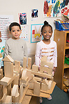 Education Preschool two 4 year olds posing with large block construction they built together