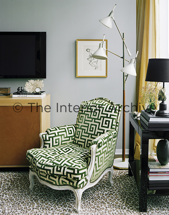 A classic armchair in the living room is given a modern twist with a bold, green geometric fabric.