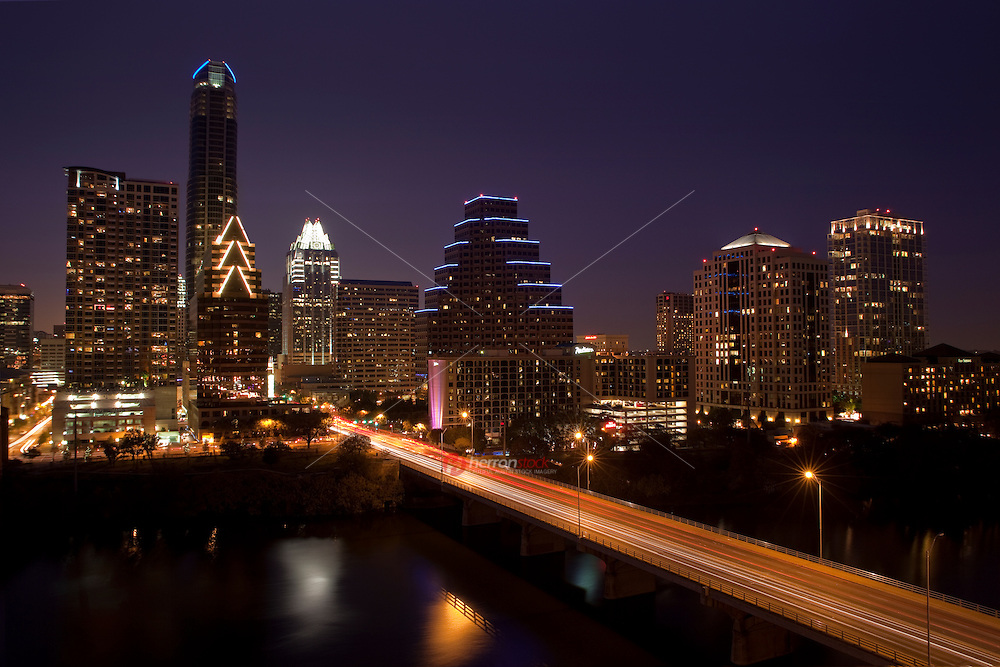 The city of Austin skyline at night as viewed across Lady Bird Lake in Austin Texas.
