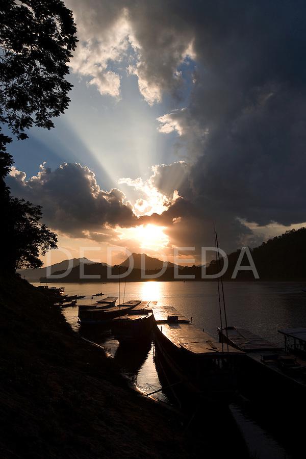Wooden river boats at sunset dock along the Mekong River at Luang Prabang, Laos.