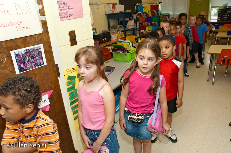 MR / Schenectady, New York. Elmer Avenue School (urban public elementary school). Kindergarten classroom. Students line up for lunch. Student with pink bag (girl, age 6, type one diabetes) has her insulin pump is in the pouch on her stomach. MR: Cul1. ID: AH-gKg. ©Ellen B. Senisi