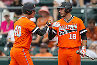 Oklahoma State Cowboys first baseman Tanner Krietemeier #16 greets teammate Craig McConaughy #40 after he scored during the NCAA baseball game against the Texas Longhorns on April 26, 2014 at UFCU Disch–Falk Field in Austin, Texas. The Cowboys defeated the Longhorns 2-1. (Andrew Woolley/Four Seam Images)