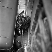 """Palais de Justice. 6 juin 1961. Vue en plongée de l'arrivée d'un des accusés : l'homme descend du fourgon cellulaire, se cache le visage avec sa main, il est encadré par plusieurs policiers. Cliché pris dans le cadre de l'affaire de la """"Tournerie des drogueurs"""" dont le procès s'est ouvert à Toulouse le 5 juin 1961. Observation: Affaire de la """"Tournerie des drogueurs"""" : Procès qui s'est ouvert aux assises de Toulouse le 5 juin 1961, sous la présidence de M. Gervais (conseiller doyen). Sur le banc des accusés se trouvent François Lopez, Raoul Berdier, Marie-Thérèse Davergne (Maïté) et d'autres malfaiteurs toulousains (Camille Ajestron, Henri Oustric, Raymond Peralo, Marcel Filiol, Paul Carrère, Charles Davant et François Borja). Outre les accusations pour association de malfaiteurs, ils comparaissent pour l'assassinat de Jean Lannelongue, propriétaire du Cabaret la Tournerie des Drogueurs (rue des Tourneurs) dans la nuit du 3 au 4 janvier 1959, au cours d'une tentative de racket."""