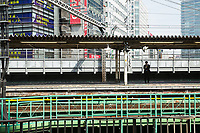 A man waits on a train platform in central Tokyo.