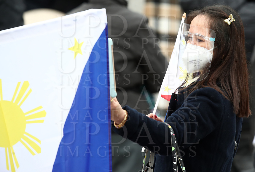 A woman wearing face mask to curb the spread of COVID-19, uses her phone as Pope Francis recites the Angelus noon prayer from the window of his studio overlooking St.Peter's Square, at the Vatican, Sunday, March 14, 2021.<br /> UPDATE IMAGES PRESS/Isabella Bonotto<br /> <br /> STRICTLY ONLY FOR EDITORIAL USE