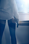 Sensual closeup of a sexy woman standing by the window with a gun in her hand wearing a mens dress shirt and stockings looking out into the night Image © MaximImages, License at https://www.maximimages.com