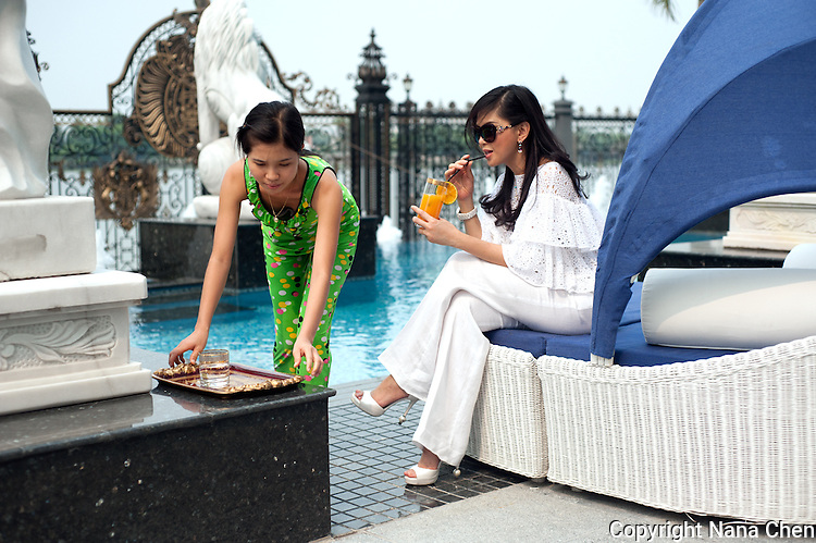 Former film actress and one of Vietnam's wealthiest women, Thuy Tien is the president of Imex Pan Pacific, a trading company that runs over 26 major businesses, including shopping malls, duty free fashion designer boutiques. Pictured here in her high security riverside villa in Anphu, Saigon, a residential enclave with rich Vietnamese and expats. Pictured here with one of her maids on left. Thuy Tien is in Chanel and Bvlgari jewellery and accessories.