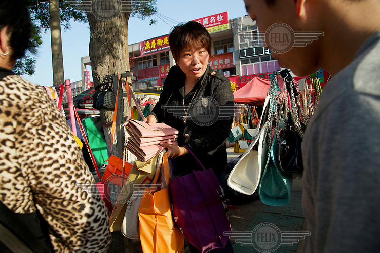 A former rural resident buys a handbag on the outskirts of Liaocheng. They are moved from their farmland several years ago and resettled nearby in purpose-built estate. China is hoping by relocating farmers into cities they would start to buy food, making a break from the cycle of farmers consuming only what they produce. The Chinese government plans to move 250 million rural residents into urban areas over the coming dozen years though it is unclear whether people want to move and where the money for this project will come from. Further urbanisation is meant to drive up consumption to counterbalance an export orientated economy and end subsistence farming but the drive to get people off the land is causing tens of thousands of protests each year. /Felix Features