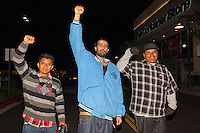 Three Occupy Santa Ana protestors hold their fists in the air in front of The Container Store during a march early in the morning (1:24am) on Black Friday.  The man in the center is Arman, and on the right is Alex.