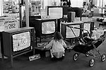 """Multi ethnic Britain 1970s, white girls pushing black British baby in a pram around a department store London 1972.<br /> Uk department store selling televisions Signs say """"Purchase Tax Cuts"""". Dickie Davies ITV World of Sport TV presenter is on the telly."""