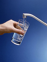 Kitchen faucet delivers clean, clear water into drinking glass.