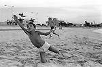 Mazatlan Mexico 1973. Local boy playing Frisbee with American men on beach. The boy is holding a small tame bird he has caught in his left hand. 1970s