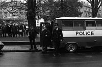 """""""Portai [Portay], Picard, Me Cathala, Me Bouscatel, Me Rastoul"""". Place Wilson. 30 novembre 1976. Vue d'ensemble de policiers sortant d'un fourgon de police, au centre un homme tient un dossier (juge d'instruction M. Ducasse?) ; en arrière-plan square, des personnes regardent la scène, enseigne """"Gaumont"""". Cliché pris le jour d'une reconstitution judiciaire dans le cadre de l'affaire du meurtre de René Trouvé. Observation: Affaire René Trouvé-Birague : le 19 février 1976, le journaliste René Trouvé est assassiné d'une balle dans la tête, par deux inconnus, alors qu'il regagne son domicile au 33 rue Bayard."""