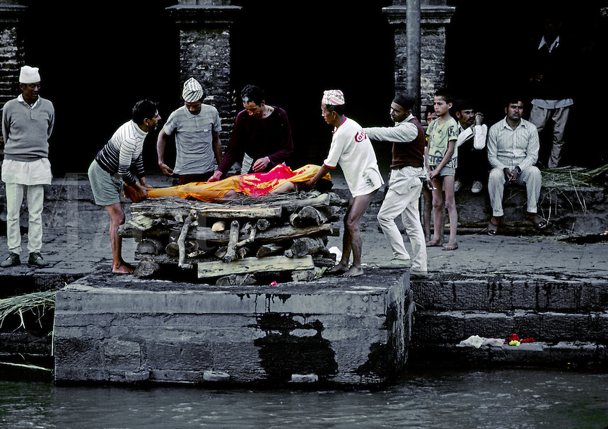 A human body is layed on a CREMATION GHAT at the Hindu Temple complex of PASHUPATINATH where the ashes will be swept into the BAGMATI RIVER - KATHAMANDU, NEPAL
