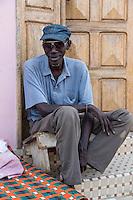 Senegal, Saint Louis.  Middle-aged Senegalese Man Sitting at his Front Door.
