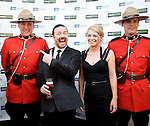 BANFF, AB, CANADA - JUNE 15:  Actor Ricky Gervais, second left, with partner Jane Fallon posing for photos with Canadian Mounted Police on the red carpet before the 2010 Banff World Television awards on June 15, 2010 at the Banff Springs Hotel in Banff, Alberta, Canada. Photo by Jimmy Jeong *** Local Caption *** Ricky Gervais