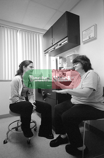 Middle age woman gesturing with hands seated in examination room with young female internal medicine resident physician listening