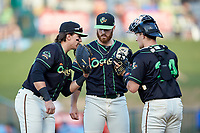 Ocelotes de Greensboro first baseman Mason Martin (left) has a meeting on the mound with starting pitcher Colin Selby (38) and catcher Grant Koch (34) during the game against the Hickory Crawdads at First National Bank Field on June 11, 2019 in Greensboro, North Carolina. The Crawdads defeated the Ocelotes 2-1. (Brian Westerholt/Four Seam Images)