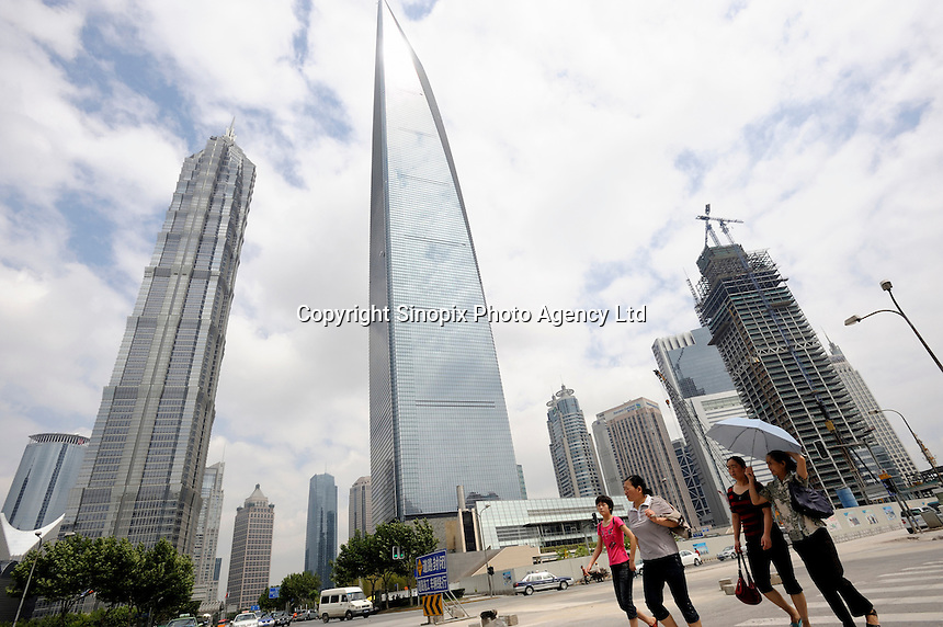 Chinese women walk past Shanghai World Financial Center and Jinmao Tower in Pudong, Shanghai, China..