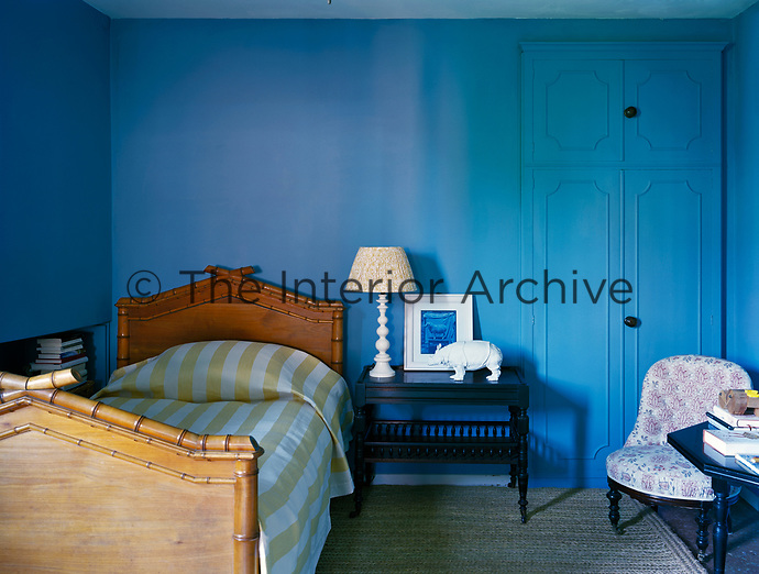 A striking blue bedroom is simply furnished with a bamboo-style wooden bed and black-painted side tables