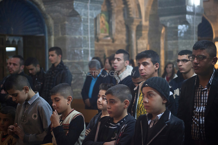 16/11/14. Alqosh, Iraq. Wassam (front, second right) attends a service with orphans and residents of Alqosh in the monastery's Der Saida Church.