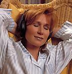 Junge Frau mit Kopfhoerern lehnt im Korbstuhl zurueck, die Augen geschlossen | young woman with headphones sitting in a cane chair, eyes closed