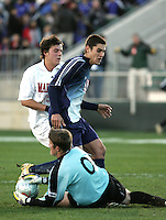 SMU goalkeeper Matt Wideman (0) gathers the ball as Ryan Mirsky (11) shields Maryland's Marc Burch (15). The University of Maryland Terrapins defeated the Southern Methodist University Mustangs 4-1 in a Men's College Cup Semifinal at SAS Stadium in Cary, NC, Friday, December 9, 2005.
