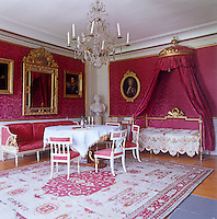 Gilt-framed family portraits hang on the walls of this salon which are covered in a deep red damask