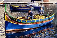 Spinola Bay, St. Julians, near Valletta, Malta.  Luzzu, Small Boat, with Fishermen.