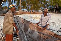Jambiani, Zanzibar, Tanzania.  Two Fishermen on the Beach with Canoe.