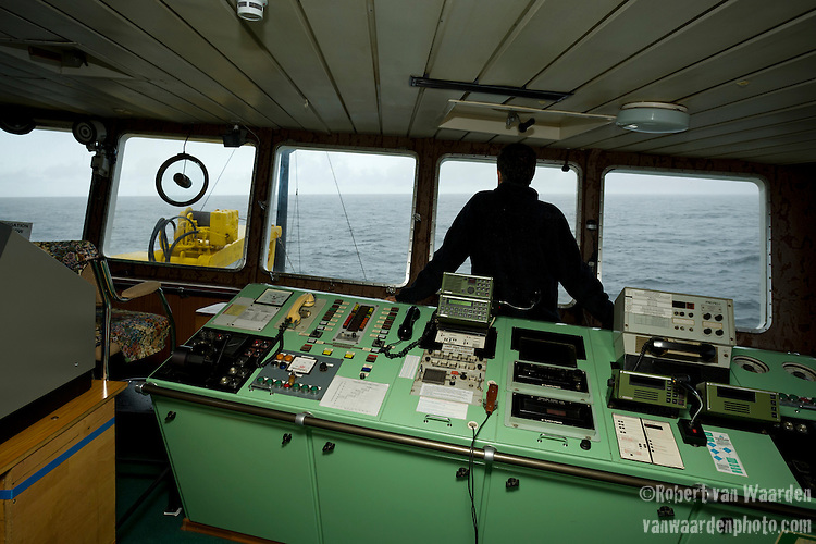 A man examines the horizon of the North Atlantic while the ship lists to starboard. The man is a scientist with the Cape Farewell Youth Expedition organized by the British Council of Canada.