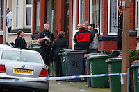 """Pictured: David Campbell (also known as David Charmers in grey coat with black sleeves) is being led away by officers from a house in Raffles Road in Birkenhead, Merseyside, where armed police have placed a containment on a terraced house.<br />Re: Armed police have been called to a disturbance at a house on Merseyside.<br />A large number of officers have surrounded the home in Raffles Road, Birkenhead and have closed the road to traffic.<br />Merseyside Police described the situation as an """"ongoing police incident"""" but declined to give further details.<br />A force spokesman confirmed police arrived at about 08:10am. An ambulance is also in attendance."""