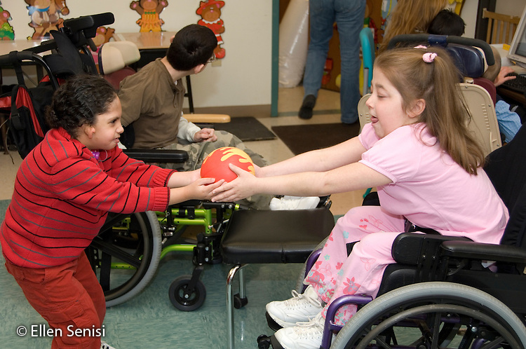 MR / Albany, NY.Langan School at Center for Disability Services .Ungraded private school which serves individuals with multiple disabilities.Boy hands ball to girl. Handling a ball helps students with grasping and coordination. Boy in red: 7, African-American, Pierre Robin syndrome, limited verbal output with expressive and receptive language delays; Girl: 11, cerebral palsy, non verbal with expressive and receptive language delays.MR: Gor3, Smi24.© Ellen B. Senisi