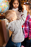 Education Preschool 3-4 year olds boy using his hand to compare heights with female classmate, another girl looking on