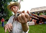 ROXBURY CT. 11 July 2015-071115SV02-Aurel Plouffe of Wolcott plays a tune while warming up during the annual Pickin' 'N' Fiddlin' fundraiser at Hurlburt Park in Roxbury Saturday.<br /> Steven Valenti Republican-American