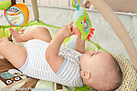 5 month old baby boy reaching up to grasp toy dangling from toy bar