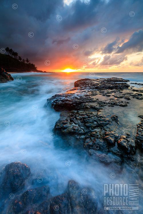 Sunset reflects on the sea washing around and over large lava rocks at Secret Beach, Kilauea, Kaua'i.