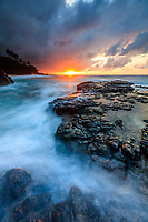 Sunset reflects on the sea washing around and over large lava rocks at Secret Beach, Kilauea, Kaua'i.