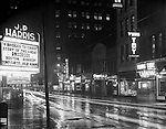 Pittsburgh PA:  View south on Sixth Street toward Liberty Avenue. Local business signs lighting up Sixth Ave include; Harris Theatre, BK Elliott Company, Dines Bar, Leo's Flowers, Richest Restaurant, Thompson's Cafeteria, and Yung Toy Restaurant.