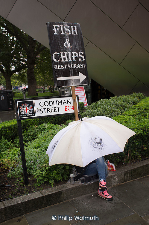 Tourist with an umbrella in the City Of London in heavy rain.
