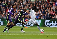 SWANSEA, WALES - MAY 17: Bafetimbi Gomis of Swansea (R) takes a shot, marked closely by Martin Demichelis (L) and Eliaquim  Mangala (C) of Manchester City during the Premier League match between Swansea City and Manchester City at The Liberty Stadium on May 17, 2015 in Swansea, Wales. (photo by Athena Pictures/Getty Images)