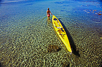 A girl in a pink swimsuit wades through clear water pulling a yellow kayak at Olowalu, Maui.