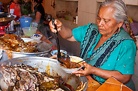 Tlacolula, Oaxaca, Mexico.  Tlacolula Restaurant.  Woman Ladling Barbecued Goat Soup into a Bowl.  Lunch.