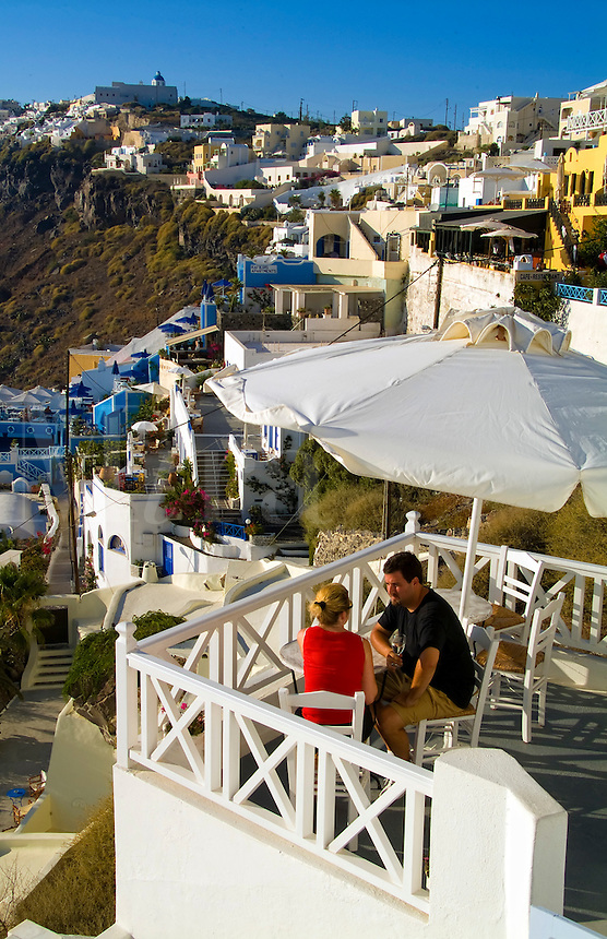 Santorini Greece and the beautiful white buildings on the mountain cliffs of main city of Fira and romantic couple relaxing on terrace